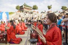 Gli studenti cinesi e stranieri con una benedizione del hanfu si sono riuniti nella torre di orologio alla cerimonia Immagine Stock