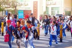 Gli studenti cinesi si dirigono dopo la scuola attraverso l'intersezione di traffico fotografia stock libera da diritti