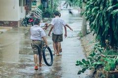 Gli studenti del ragazzo lasciano l'aula per camminare sulla via dopo pioggia persistente immagine stock libera da diritti