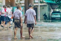 Gli studenti del ragazzo lasciano l'aula per camminare sulla via dopo pioggia persistente fotografia stock libera da diritti