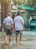 Gli studenti del ragazzo lasciano l'aula per camminare sulla via dopo pioggia persistente immagini stock