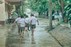 Gli studenti del ragazzo lasciano l'aula per camminare sulla via dopo pioggia persistente fotografia stock