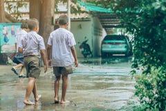 Gli studenti del ragazzo lasciano l'aula per camminare sulla via dopo pioggia persistente fotografie stock libere da diritti