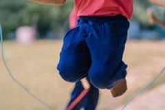 Gli studenti della scuola elementare godono dell'addestramento di salto della corda per il buon hea Fotografia Stock