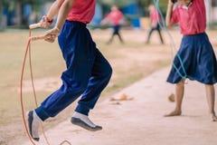 Gli studenti della scuola elementare godono dell'addestramento di salto della corda per il buon hea Fotografie Stock Libere da Diritti