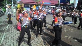 Gli studenti della scuola si sono vestiti nell'incrocio dei passaggi di dancing della polizia Immagine Stock