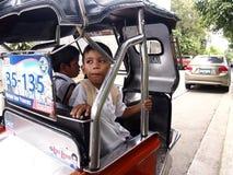 Gli studenti dentro la carrozza di un triciclo aspettano l'autista per prenderli domestici dalla scuola Fotografia Stock Libera da Diritti