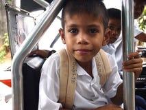 Gli studenti dentro la carrozza di un triciclo aspettano l'autista per prenderli domestici dalla scuola Immagine Stock