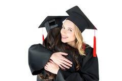 Gli studenti felici nella graduazione ricopre abbracciare isolati su bianco Fotografie Stock Libere da Diritti