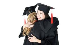 Gli studenti felici nella graduazione ricopre abbracciare isolati su bianco Immagini Stock