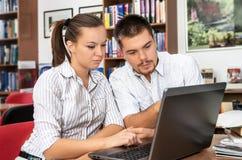 Gli studenti imparano online in una biblioteca Immagini Stock