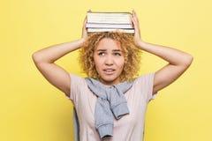 Gli studenti infelici sta tenendo alcuni libri sulla sua testa Sta tenendoli con le sue mani Sembrare del ` t del doesn della rag Fotografia Stock Libera da Diritti
