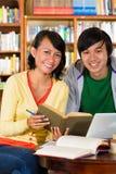 Gli studenti in libreria sono un gruppo d'apprendimento Immagini Stock Libere da Diritti