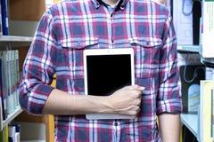Gli studenti maschii usano la tecnologia per trovare i libri per leggere dentro la biblioteca Concetto di formazione immagini stock libere da diritti