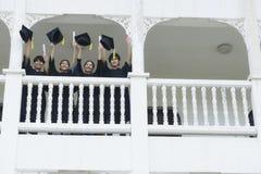 Gli studenti nel ritenere soddisfatti degli abiti di graduazione stanno al corrido Fotografie Stock Libere da Diritti
