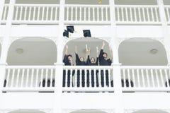Gli studenti nel ritenere soddisfatti degli abiti di graduazione stanno al corrido Fotografia Stock