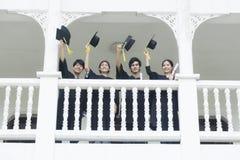 Gli studenti nel ritenere soddisfatti degli abiti di graduazione stanno al corrido Immagini Stock Libere da Diritti