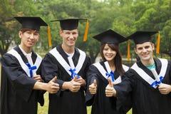 gli studenti nella graduazione abbiglia la mostra dei diplomi con i pollici Immagini Stock