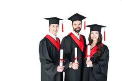 Gli studenti nella graduazione ricopre i diplomi della tenuta e sorridere alla macchina fotografica Immagini Stock Libere da Diritti