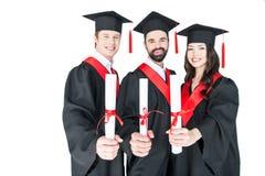 Gli studenti nella graduazione ricopre i diplomi della tenuta e sorridere alla macchina fotografica Immagini Stock
