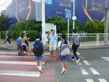 Gli studenti passano alla scuola attraverso l'intersezione di traffico Immagini Stock