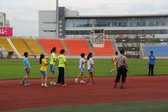 Gli studenti praticano correre nel centro sportivo Immagine Stock