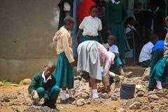 Gli studenti pubblici tanzaniani della High School lavorano nel cortile della scuola immagini stock