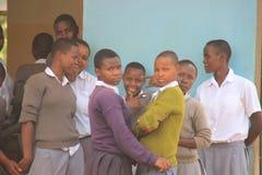 Gli studenti pubblici tanzaniani della High School in uniforme scolastico stanno sorridendo immagini stock libere da diritti