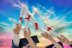Gli studenti si laurea con i cappelli ed i diplomi Fotografie Stock Libere da Diritti