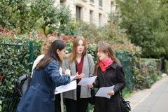 Gli studenti stranieri che imparano l'inglese con le carte si avvicinano ai Bu dell'università Immagine Stock