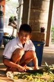 Gli studenti tailandesi che si siedono sull'uso al suolo un coltello hanno tagliato le verdure a pezzi per concimare con la compo Immagini Stock