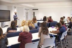 Gli studenti universitari studiano in un'aula con il conferenziere maschio Immagine Stock Libera da Diritti