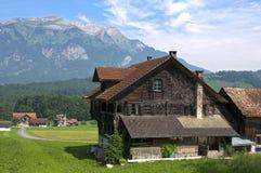 Gli svizzeri abbelliscono con le montagne e la vecchia azienda agricola di legno Immagine Stock Libera da Diritti