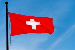 Gli svizzeri inbandierano l'ondeggiamento sopra il cielo blu Immagini Stock Libere da Diritti