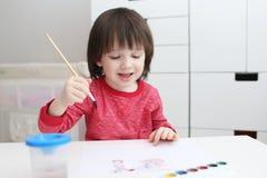 gli Tre-anni di bambino sta dipingendo Immagine Stock