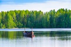 Gli uccelli si sono appollaiati su un peschereccio su un lago da un'abetaia Fotografia Stock