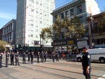 Gli ufficiali di polizia stanno nella linea attraverso la via del mercato alle sei st Fotografia Stock Libera da Diritti