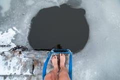 Gli uomini è gambe sul ghiaccio vicino al foro del ghiaccio immagine stock libera da diritti