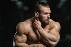 Gli uomini atletici del forte culturista brutale che pompano su muscles con la d Immagini Stock