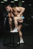 Gli uomini atletici del forte culturista brutale che pompano su muscles con la d Immagine Stock Libera da Diritti