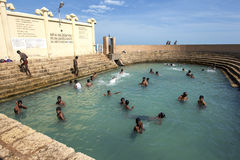 Gli uomini bagnano a Vali North Pradeshiya Sabha (bagno sacro di Keerimalai) nella regione di Jaffna di Sri Lanka Fotografie Stock