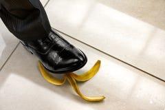 Gli uomini calzano fare un passo sulla buccia della banana Fotografie Stock Libere da Diritti