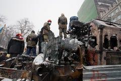 Gli uomini in caschi e nelle maschere stanno sopra le automobili militari rotte e bruciate sulla città d'occupazione dell'inverno  Fotografia Stock