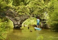 Gli uomini che galleggiano sotto il vecchio ponte su SUP imbarcano Fotografia Stock Libera da Diritti
