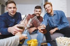 Gli uomini che guardano lo sport sulla TV a casa incoraggia insieme lo sguardo della macchina fotografica Immagini Stock Libere da Diritti