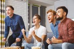 Gli uomini che guardano lo sport sulla TV a casa team insieme vinto immagini stock