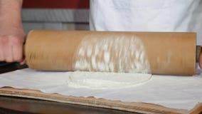 Gli uomini che il ` s passa il cuoco unico presentano sulla tavola uno strato sottile di pasta Equipaggi l'uso un matterello srot stock footage