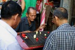 Gli uomini cinesi anziani giocano gli scacchi Fotografia Stock