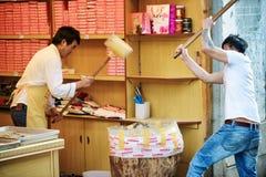 Gli uomini cinesi con i magli di legno stanno schiacciando i dadi per fare i dolci Immagine Stock