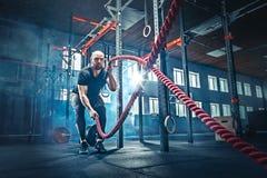 Gli uomini con la corda di battaglia combattono le corde si esercitano nella palestra di forma fisica immagini stock